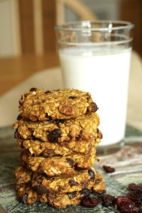 Oatmeal Cookies stacked in front of a glass of milk