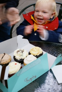 Boy clapping with cupcakes