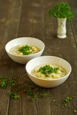 two bowls of chowder on a wooden table