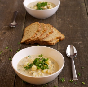 two bowls of chowder with slices of bread
