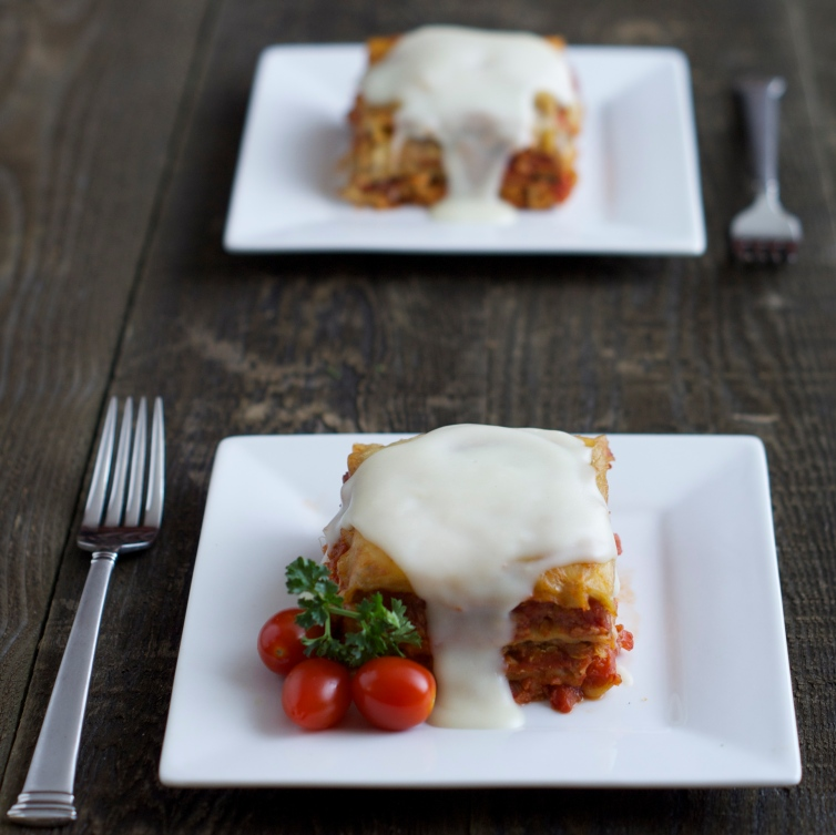 Two servings of lasagna with a tomato garnish