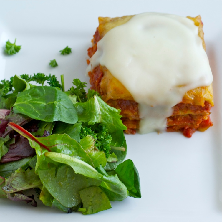 serving of lasagna with a side salad