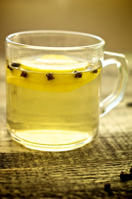 Mug of hot whiskey with cloves and lemon