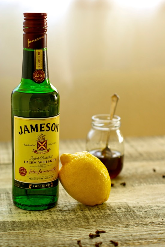 bottle of Jameson with a lemon and jar of honey