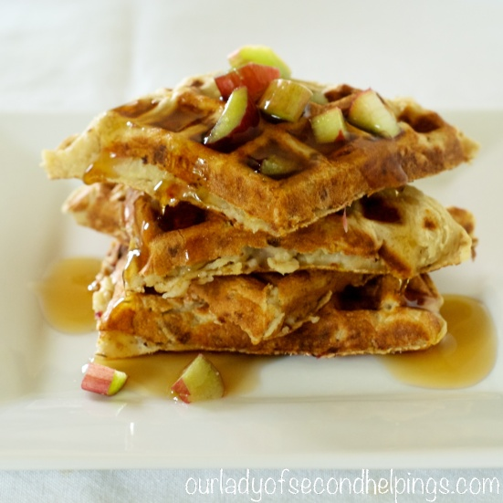 Plated waffles with rhubarb pieces and syrup